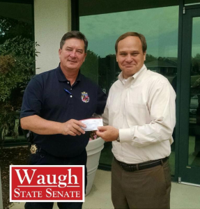 Cpl. William Raddatz displays his police badge while passing a check to GOP candidate Steve Waugh.  Photo courtesy of Waugh campaign.