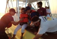 Crew from Station Chincoteague assist an injured woman onto their 24-foot Special Purpose Craft. The pleasure craft CHASER ran aground during the 2015 Chincoteague Pony Swim with six adults on board and two children.